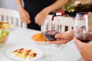 Pouring red wine for guest